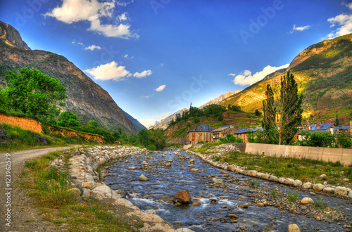 Colorful l HDR image of a pastoral village with a river on a background on mountains near Benasque (Huesca, Spain)
