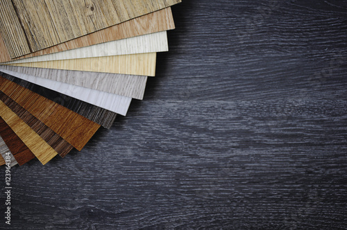 Obraz Laminate Wood Concept - Sample pack of wooden flooring laminate on wooden black floor - fototapety do salonu
