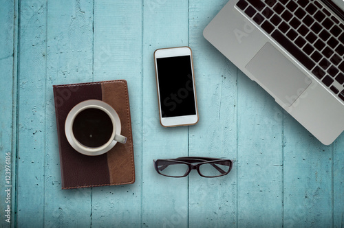 Office desk wood with computer, note book,phone and coffee cup concept in wood background.Copy space