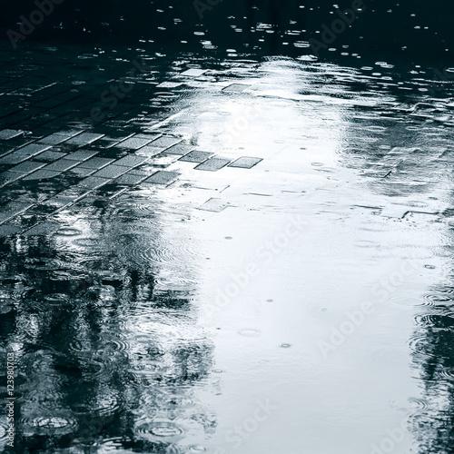 Fotografía street sidewalk with water puddles after heavy rain