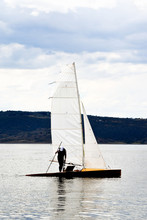 Man Standing On A Sail Boat On A Calm Lake