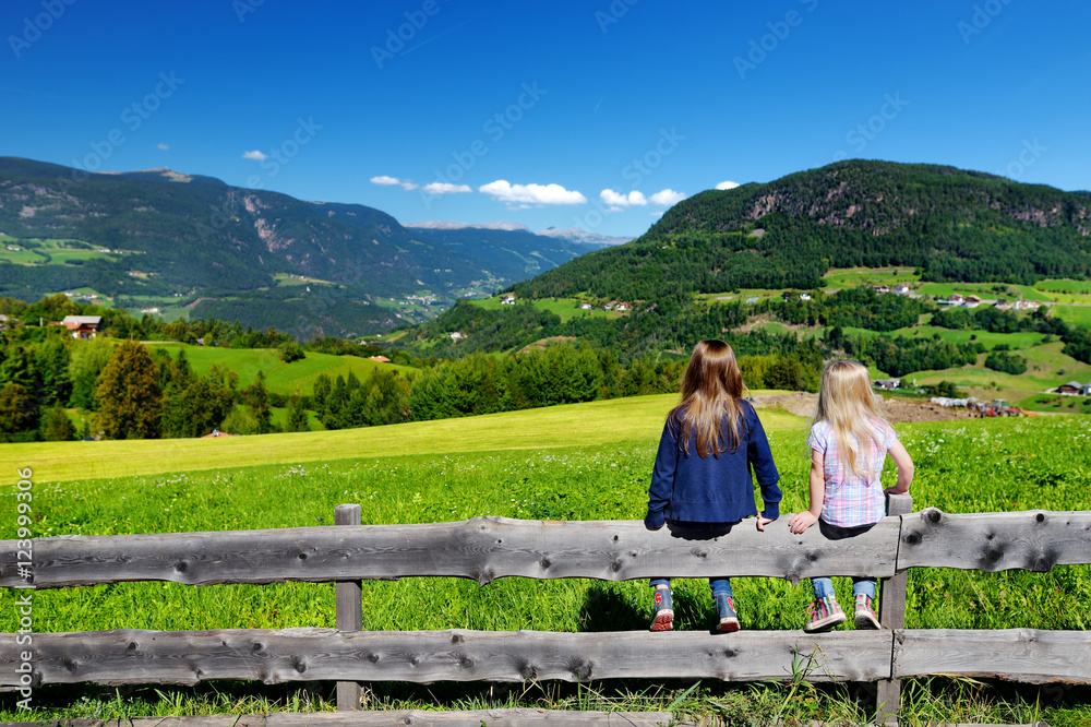 Zwei adorable kleine Schwestern, die schöne Landschaft von Dolomit ...