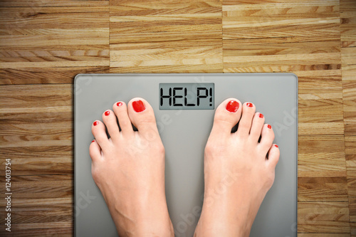 Foto Time to start a diet with women's feet on a scale, saying HELP