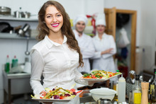 Female Waiter Taking Dish At Kitchen
