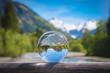 Leinwandbild Motiv Bergpanorama mit Gebirgsbach spiegelt sich in einer Glaskugel