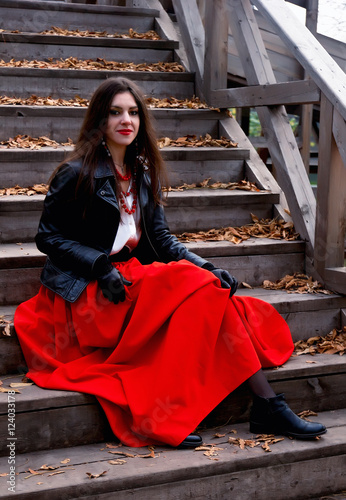 Fotografija  Young dark-haired woman in a black leather jacket and a bright beads sits liftin