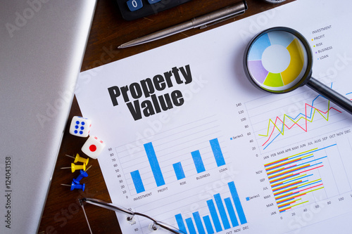 """Photo """"Property Value"""" text on paper sheet with magnifying glass on chart, dice, spect"""