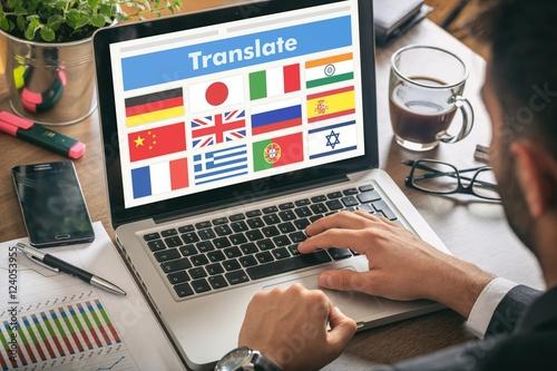 Cuadros en Lienzo  Man working on a laptop - translate on the screen