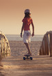 A Young Person Skateboarding With Bare Feet Over A Wooden Boardwalk Towards The Beach; Tarifa, Cadiz, Andalusia, Spain