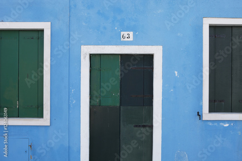 Green Wooden Shutters And Door On A Blue Painted Wall; Burano, Venezia, Italy