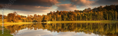 Trees Lining The Water's Edge Reflected In The Water In Autumn; North Yorkshire, England