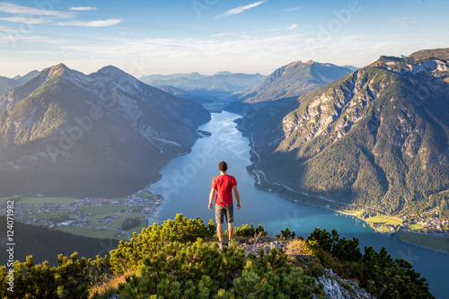 Fotografie, Obraz  Mountaineer enjoying the view over lake Achensee in summer, Austria Tyrol