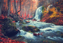 Autumn Forest With Waterfall At Mountain River At Sunset. Colorful Landscape With Trees, Stones, Waterfall And Vibrant Red And Orange Foliage. Nature Background. Fall Woods. Vintage Toning