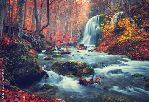 Foto auf Gartenposter Wasserfalle Autumn forest with waterfall at mountain river at sunset. Colorful landscape with trees, stones, waterfall and vibrant red and orange foliage. Nature background. Fall woods. Vintage toning