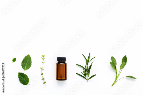 Fotografie, Obraz  Bottle of essential oil with  fresh herbal sage, rosemary, thyme