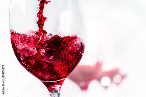 Foto op Canvas Alcohol Macro close up of red wine pouring in to glass.