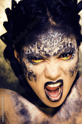 fashion portrait of pretty young woman with creative make up like a snake, halloween look