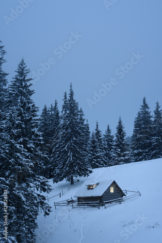 Winter landscape with wooden house in the mountains