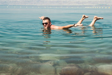 Man In Sunglasses Poses Like Airplane On Surface Dead Sea. Free Time, Vacation, Wellness Tourism, Recreation Concept.