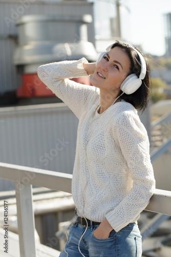 Deurstickers Ontspanning Woman in white earphones listen music at city background