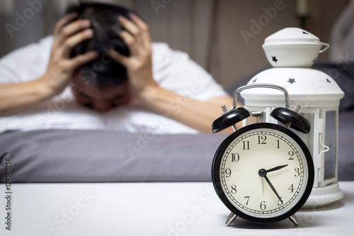 Plakat azjatycki człowiek w łóżku cierpiąc na bezsenność i zaburzenia snu myśląc o swoim problemie w nocy