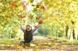 kleiner Junge wirft bunte Blätter hoch, Herbstallee