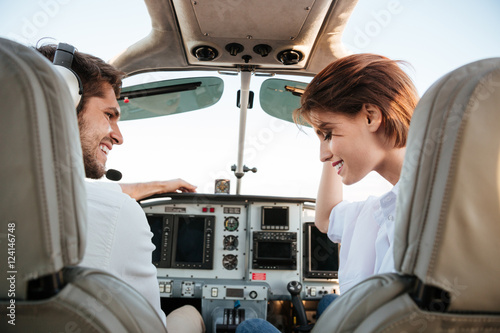 Fototapeta Couple looking at each other while sitting inside airplane cabin