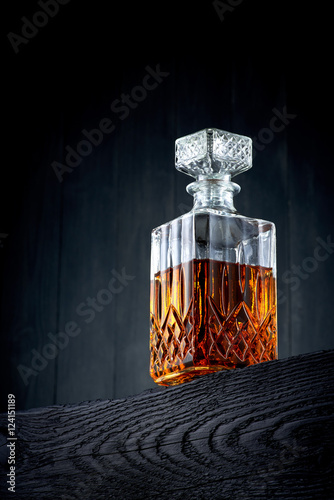 Carafe of whiskey on a black wooden table
