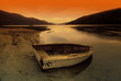 Row Boat At Water's Edge Against Sunset Backdrop