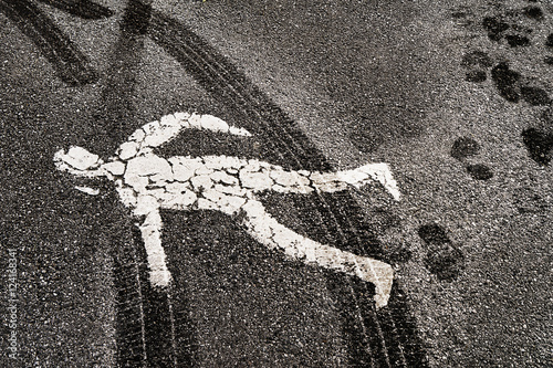 Pedestrian road figure covered in tire track marks