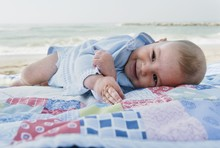 A Baby Boy Laying On A Blanket On The Beach; Benalmadena Costa, Costa Del Sol, Malaga, Andalusia, Spain
