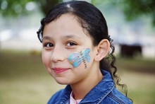 A Girl With A Butterfly Painted On Her Face
