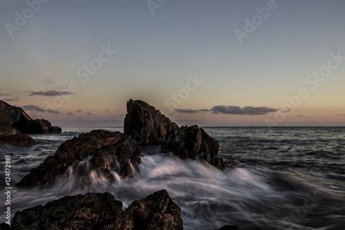 scogliera in mezzo al mare con sullo sfondo le ultime luci del tramonto