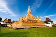 Religious Architecture And Landmarks. Golden Buddhist Pagoda Of Phra That Luang Temple Under Blue Sky. Vientiane, Laos Travel Landscape And Destinations