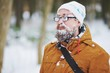 beard man in eyeglasses covered by snow enjoying cold weather.
