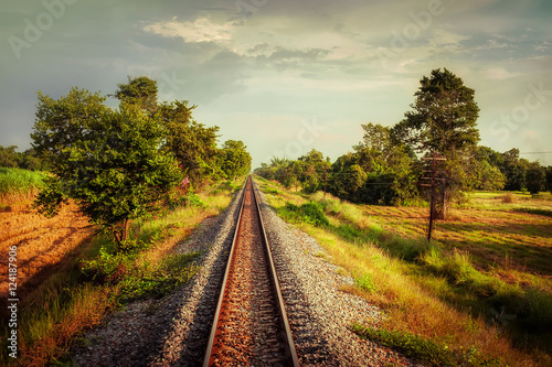 Poster Voies ferrées Railway track crossing rural landscape under evening sunset sky. Travel concept in vintage style