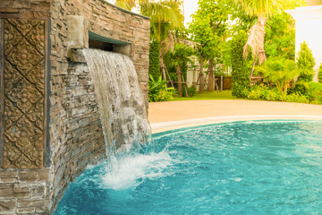 Small artificial waterfall in the swimming pool