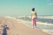 Woman is walking along the beach