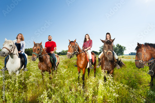 Poster Equitation Happy equestrians riding horses in summer field