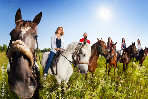 Poster Equitation Group of equestrians riding their horses in field