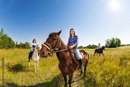 Poster Equitation Three female equestrians riding horses in field
