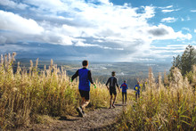 Group Of Runners Running Mountain Trail Of Mud And Stones. Autumn Yellow Grass And Blue Sky