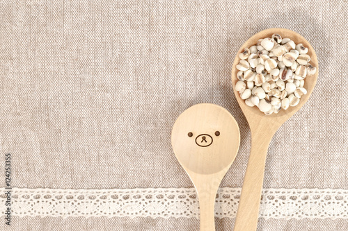 Fotografia, Obraz  jobs tears grain seed with wooden spoon isolated on food mat, for background