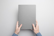 Hand Is Holding Gray Notebook