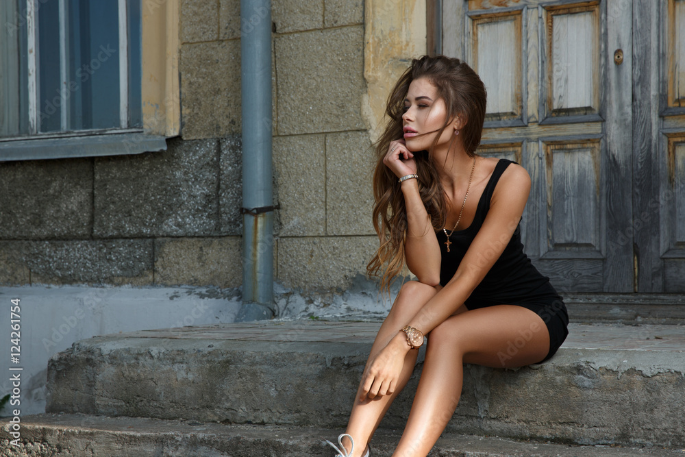Fototapety, obrazy: Young beautiful and sexy girl with slim sun tanned attractive body dressed in a slinky black singlet is posing outdoor sitting on the steps and looking into the distance in the summer city.