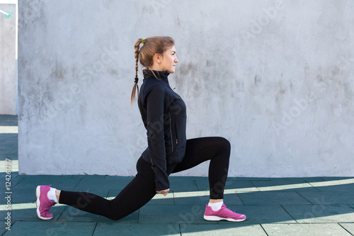 Photo Fitness woman doing front  lunge, gray wall background