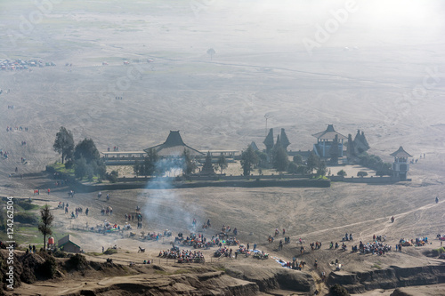 Fototapeta Looking down at the misty morning of caldera sea-sand plain from Mount Bromo. Tourist can be seen flocking around taking selfies, walking and horseback riding along the route to volcano crater.   obraz na płótnie
