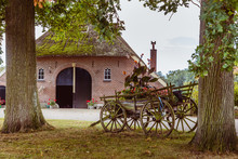 Old Farmhouse And Wooden Chariot Flowerbed