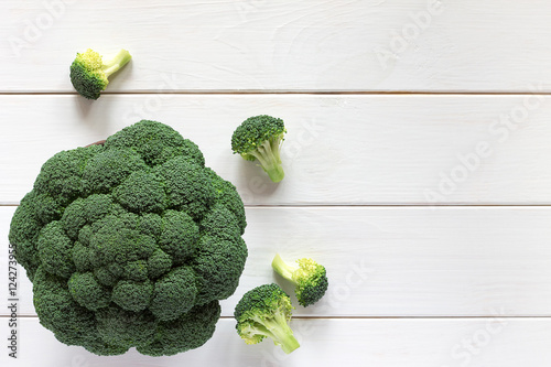 Fresh broccoli on a wooden table, top view.