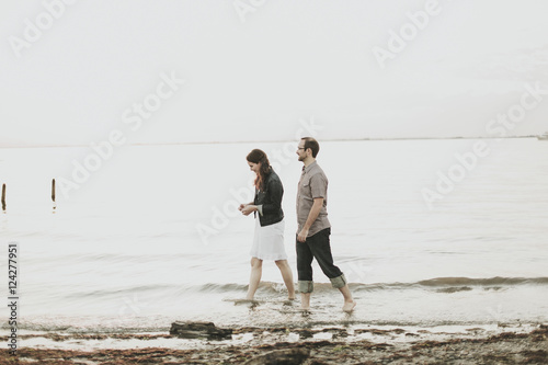 A Couple Walking Barefoot Along The Water's Edge; Crescent Beach, British Columbia, Canada